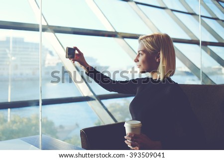 Young hipster girl is photographing herself on cell telephone, while is relaxing in modern coffee shop near sea port. Attractive woman with take away coffee is taking pictures with smart phone camera