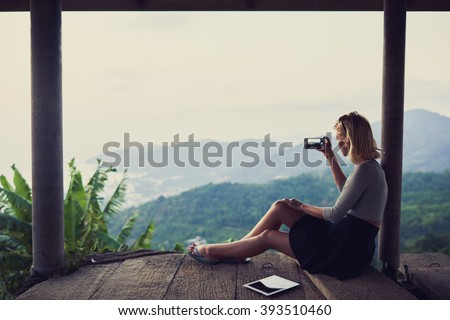 Young woman wanderer is shooting video on her mobile phone, while is sitting against subtropical landscape and sky background with copy space for your advertising text message or promotional content
