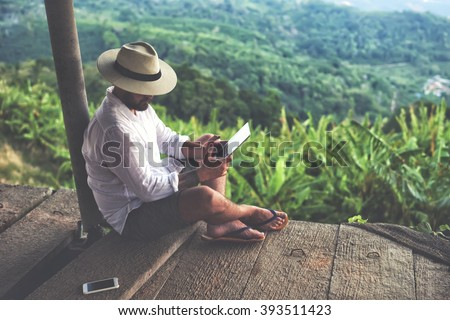 Man traveler is using digital tablet, while is sitting against beautiful Asian scenery during summer journey. Male wanderer is holding touch pad, while is relaxing outdoors during his trip in Thailand Royalty-Free Stock Photo #393511423