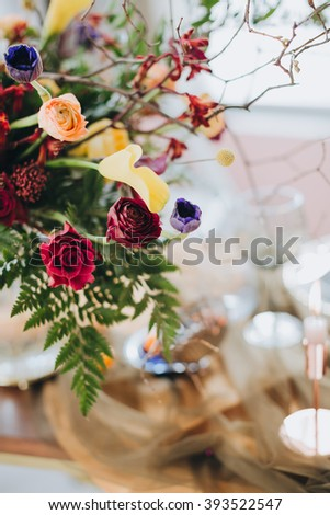 Bouquet. Bright bouquet. Artwork. Bright bouquet of red, yellow, pink, purple flowers and greenery is on the table, against a white wall #393522547