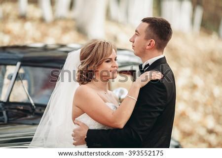 Stylish wedding couple, bride, groom kissing and hugging near retro car in autumn #393552175