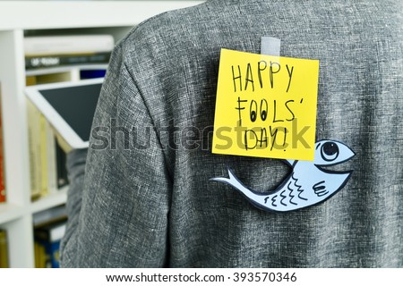 closeup of a young man with a paper fish and a note with the text happy fools day attached with tape to his back Royalty-Free Stock Photo #393570346