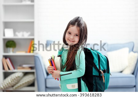 Little girl with green back pack holding stationery in living room Royalty-Free Stock Photo #393618283