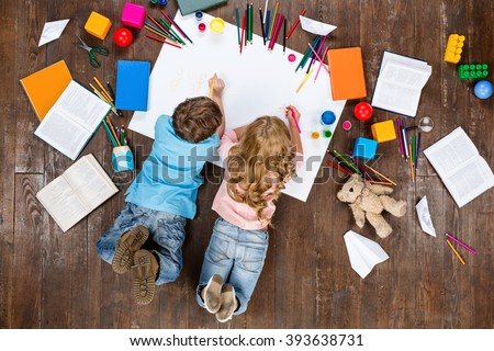 Happy children. Top view creative photo of little boy and girl on vintage brown wooden floor. Children lying near books and toys, and painting Royalty-Free Stock Photo #393638731