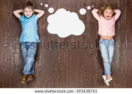 Happy children. Top view creative photo of little boy and girl on vintage brown wooden floor. Children lying near empty cloud with thoughts, looking at camera and smiling #393638761