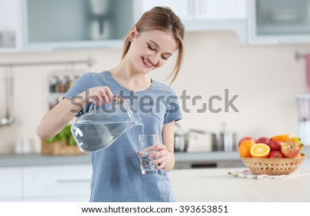 Young woman pouring water from jug into glass in the kitchen #393653851