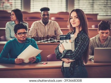 Multinational group of cheerful students taking an active part in a lesson while sitting in a lecture hall. #393668308