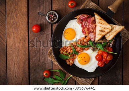 English breakfast - fried egg, beans, tomatoes, mushrooms, bacon and toast. Top view Royalty-Free Stock Photo #393676441