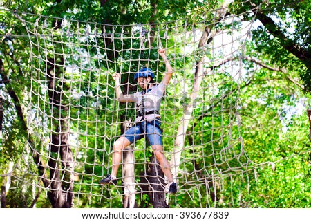adventure climbing high wire park - people on course in mountain helmet and safety equipment #393677839