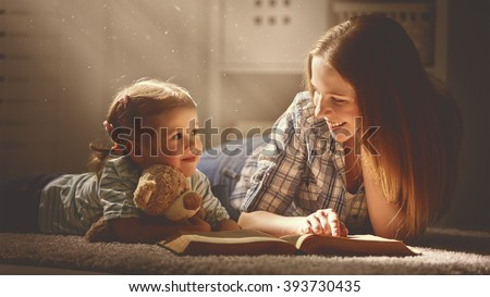 happy family mother and daughter read a book in the evening at home #393730435