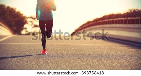 young fitness woman runner running on sunrise road #393756418