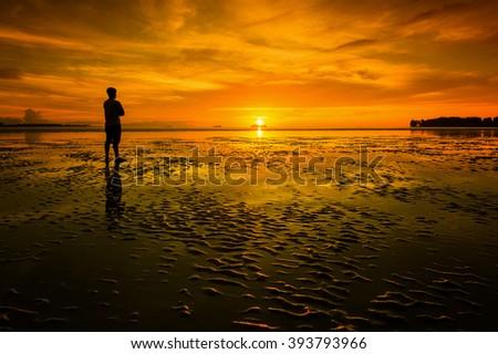 Men and sun on the beach sunset. Conceptual scene. #393793966