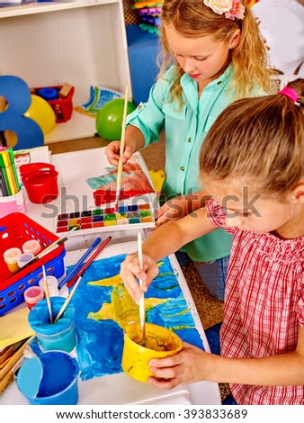 Group little girl with brush painting on table in  kindergarten . Creativity education. #393833689