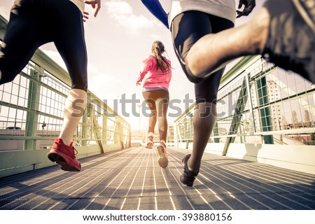 Three runners sprinting outdoors - Sportive people training in a urban area, healthy lifestyle and sport concepts Royalty-Free Stock Photo #393880156