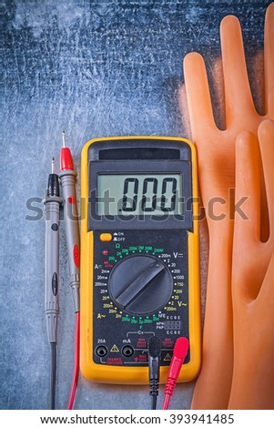 Digital multimeter dielectric rubber gloves on metallic background vertical version electricity concept. #393941485