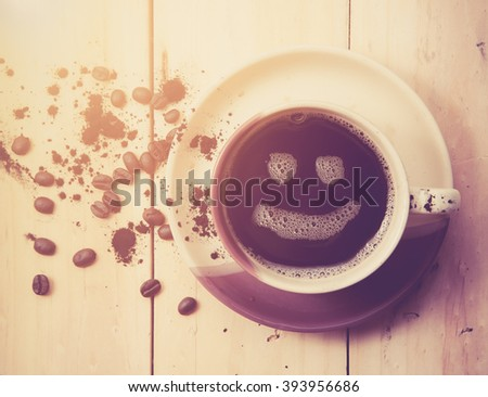 Espresso Cup with smiley face on wooden table, overhead view