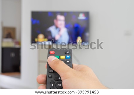 Watching TV and using remote controller #393991453