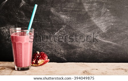 Healthy pomegranate and yogurt smoothie rich in vitamin c and dietary fiber with fresh fruit alongside on a rustic table with copy space on an old slate chalkboard #394049875