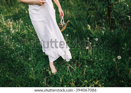 girl in white dress with bare feet is walking on grass in the garden #394067086