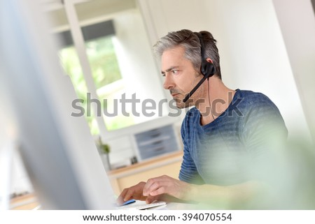 Businessman in office using phone headset #394070554