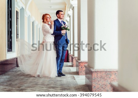 Wedding portrait of a bride and groom outdoor among columns #394079545