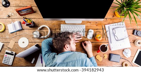 Businessman sleeping on the desk, office gadgets and supplies