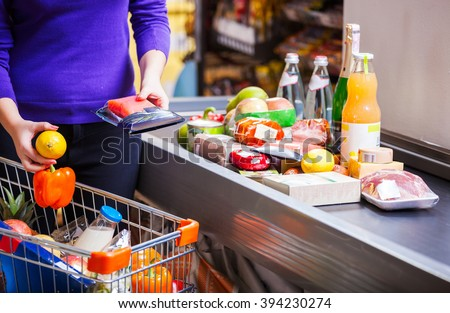 Young woman putting goods on counter in supermarket Royalty-Free Stock Photo #394230274