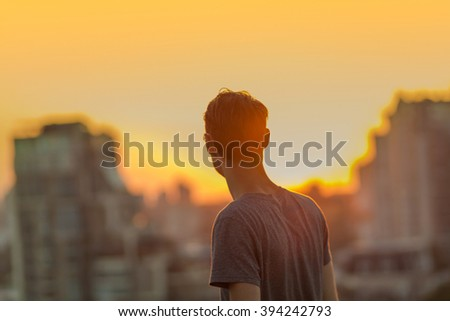 Defocused cityscape background. Gorgeous warm bokeh. Man on the sunset background. #394242793