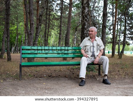 Old man sitting on the bench in park against trees as a background. #394327891
