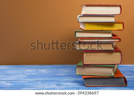 Stack of hardback books on wooden table. Back to school. Copy space for text #394338697