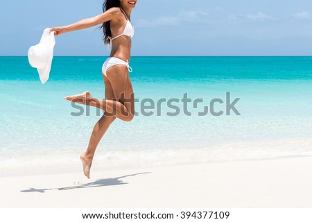 Beach ready bikini body - sexy slim legs and toned thighs and butt. Suntan happy woman jumping in freedom on white sand with sun hat. Weight loss success or epilation concept. #394377109