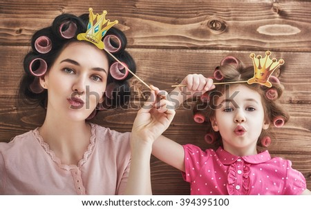 Funny family! Mother and her child daughter girl with a paper accessories. Beauty funny girl holding paper crown on stick. Beautiful young woman holding paper crown on stick.