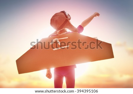 Little child girl plays astronaut. Child on the background of sunset sky. Child in an astronaut costume plays and dreams of becoming a spaceman. Royalty-Free Stock Photo #394395106