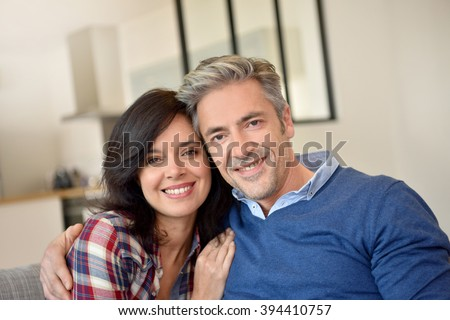 Middle-aged couple relaxing in sofa at home #394410757