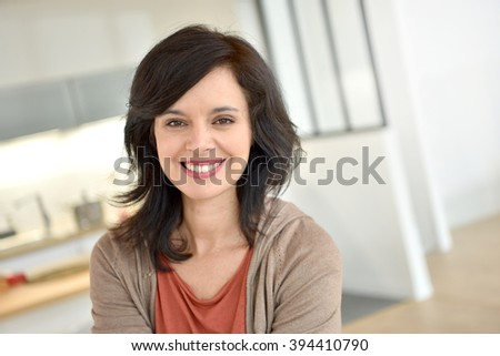 Portrait of smiling 40-year-old woman at home #394410790