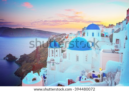 vew of Oia, traditional greek village of Santorini,  with blue domes of churches at sunset, Greece, toned #394480072