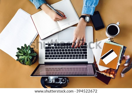 stylish young girl working  analytics holding pen on craft background with laptop and papers flat lay #394522672