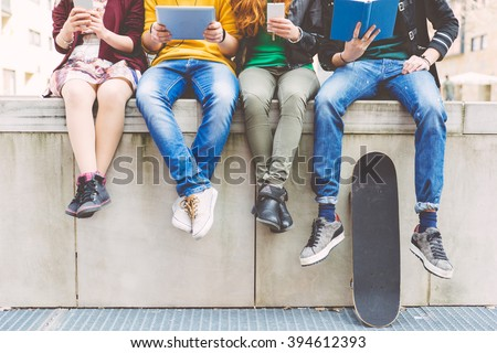 Group of teenagers making different activities sitting in an urban area Royalty-Free Stock Photo #394612393