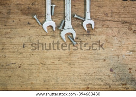 Wrench on the brown wooden background #394683430
