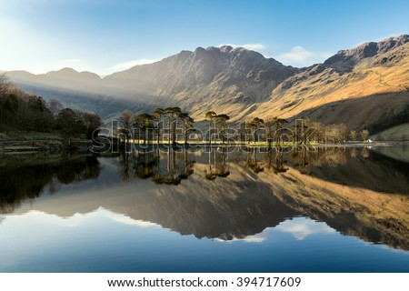 Beautiful morning sunlight shining on Buttermere in the Lake District with mirror like reflections.  #394717609