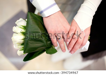 Bride and groom hands with engagement rings and bridal bouquet #394734967