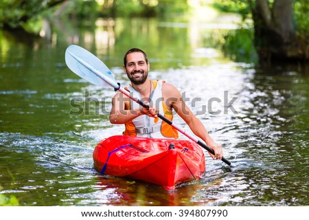 man driving with kayak on forest river #394807990