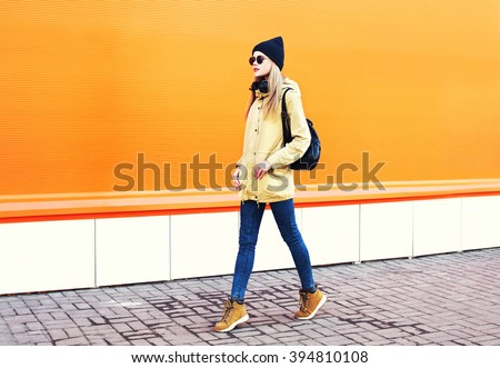 Fashion pretty blonde woman walking in city over colorful orange background #394810108