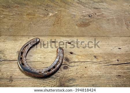 lucky horseshoe, used and with rust, on rustic wooden planks, symbol for good luck, background with copy space #394818424
