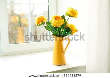 yellow flowers in a yellow vase on a windowsill #394933579