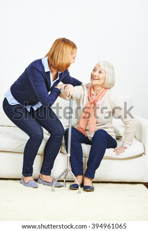 Woman helping senior woman with cane getting up from a sofa #394961065