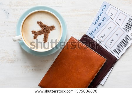 Airplane made of cinnamon in coffee.  Cup of coffee, passports and no name boarding passes. Traveling concept. Cappuccino in airport  Royalty-Free Stock Photo #395006890