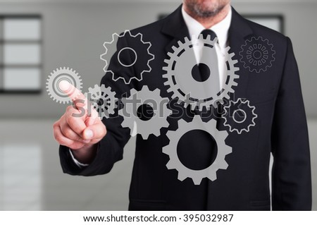 Businessman finger touching a modern digital gear on touchscreen as business or engineering innovation concept #395032987