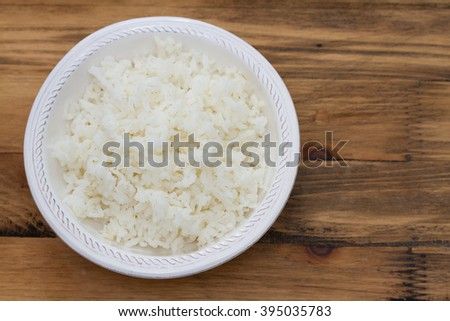 boiled rice on white bowl on brown wooden background #395035783