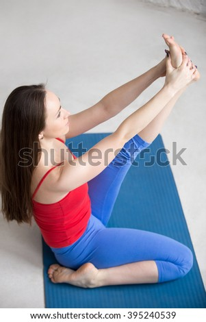 Beautiful young woman in bright colorful sportswear working out indoors in loft interior on blue mat. Girl sitting in Heron pose, Krounchasana, for legs strength and flexibility. Full length #395240539